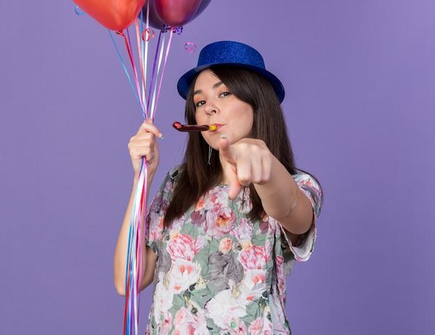 Selbstbewusste junge schöne frau mit partyhut, die luftballons hält und die partypfeife bläst, die ihnen geste isoliert auf blauer wand zeigt