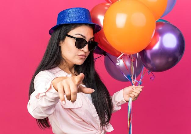 Selbstbewusste junge schöne frau mit partyhut und brille mit luftballons, die ihnen geste zeigen