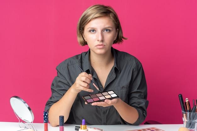 Selbstbewusste junge schöne frau sitzt am tisch mit make-up-tools und hält lidschatten-palette mit make-up-pinsel