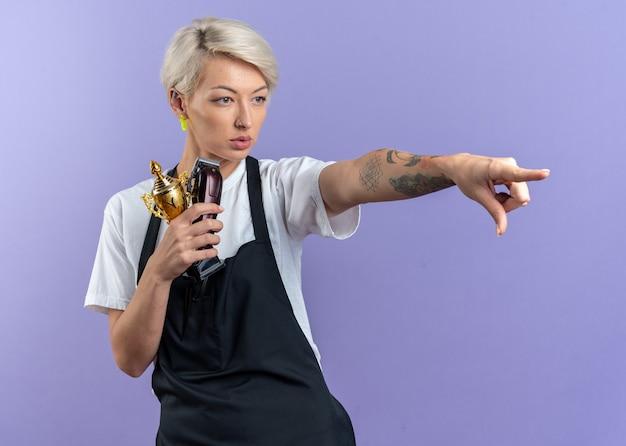 Selbstbewusste junge schöne friseurin in uniform, die siegerpokal mit haarschneidemaschinen hält, zeigt seitlich isoliert auf blauer wand blue