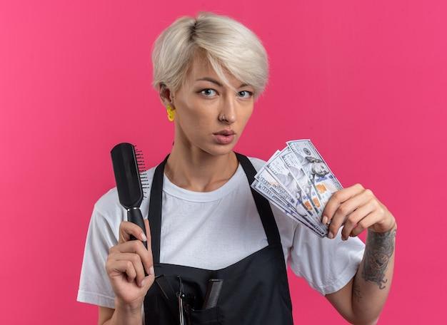 Selbstbewusste junge schöne friseurin in uniform mit kamm mit bargeld isoliert auf rosa wand pink