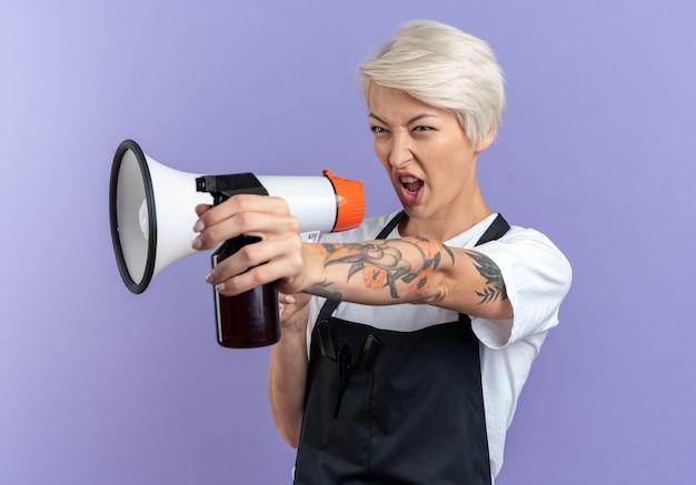 Selbstbewusste junge schöne friseurin in uniform spricht über lautsprecher, die sprühflasche an der seite isoliert auf blauer wand hält