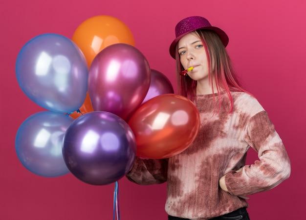 Selbstbewusste junge schöne partyhut mit ballons, die partypfeife bläst und hand auf die hüfte legt, isoliert auf rosa wand