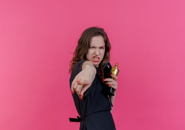 Selbstbewusste junge slawische friseurin in uniform, die haarschneidemaschinen und siegerpokal hält und zeigt