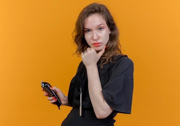 Selbstbewusste junge slawische friseurin in uniform mit haarschneidemaschine und kreditkarte, die das kinn berührt