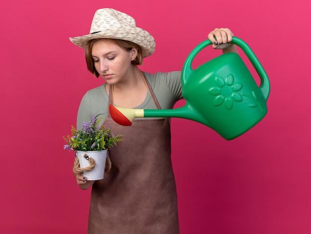 Selbstbewusste junge slawische gärtnerin mit gartenhut, die blumen im blumentopf mit gießkanne gießt