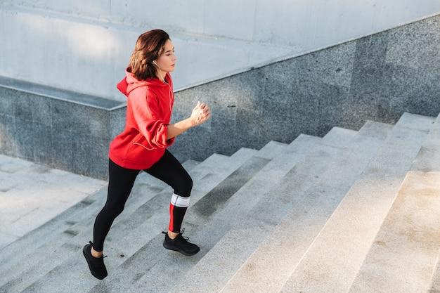 Selbstbewusste junge sportlerin, die draußen die treppe hinaufläuft