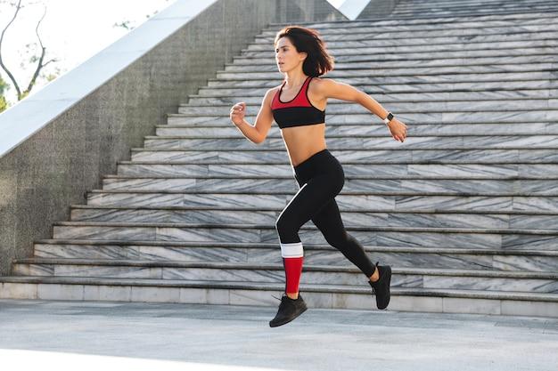 Selbstbewusste junge sportlerin, die draußen die treppe hinunterläuft