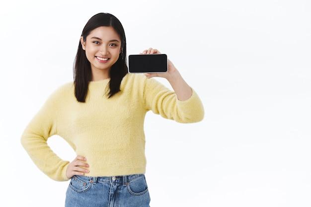 Selbstbewusste junge, süße asiatische programmiererin, die stolz ihre neue anwendung zeigt, smartphone horizontal hält, app oder spiel auf dem mobilen bildschirm fördert und erfreut über weiße wand lächelt