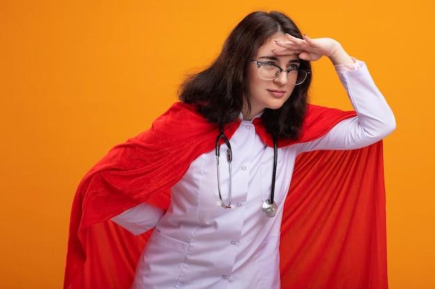 Selbstbewusste junge superheldin in arztuniform und stethoskop mit brille, die die hand hinter dem rücken und auf der stirn hält und seitlich in die ferne schaut, isoliert an der wand