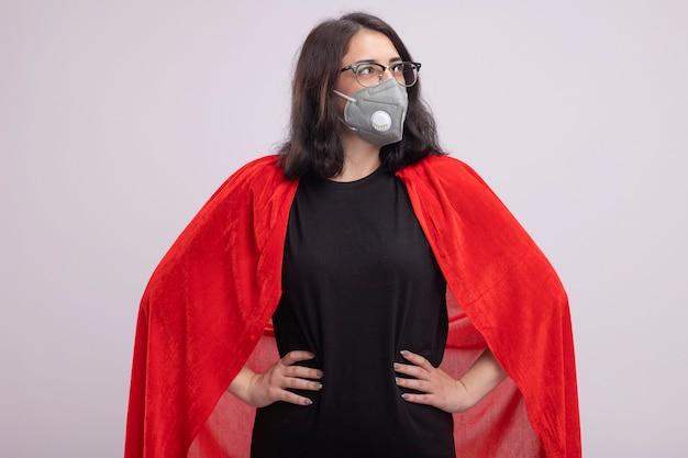Selbstbewusste junge superheldin in rotem umhang mit brille und schutzmaske, die wie ein supermann steht und die seite isoliert auf weißer wand betrachtet