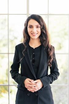 Selbstbewusste kaukasische geschäftsfrau, die einen anzug trägt, in die kamera schaut und gut gelaunt lächelt und mit unscharfen bürofenstern im hintergrund steht. vertikales foto. geschäftsfrau-porträt.
