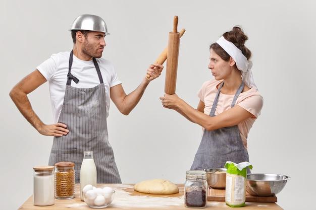 Selbstbewusste köche haben kochkämpfe, schauen sich ernsthaft an, kämpfen mit nudelhölzern, stehen seitlich neben dem küchentisch mit frischem teig und anderen zutaten, teilen kulinarische ideen