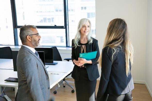 Selbstbewusste partner treffen sich im büroraum, reden und lächeln. bärtiger chef in brillen, der projekt mit schönen geschäftsfrauen bespricht. geschäfts-, kommunikations- und top-management-konzept