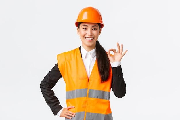 Selbstbewusste professionelle asiatische architektin im schutzhelm sichert qualität und arbeit in der zeit, zeigt gute geste und lächelt entschlossen, steht durchsetzungsfähig, sichert und garantiert etwas.