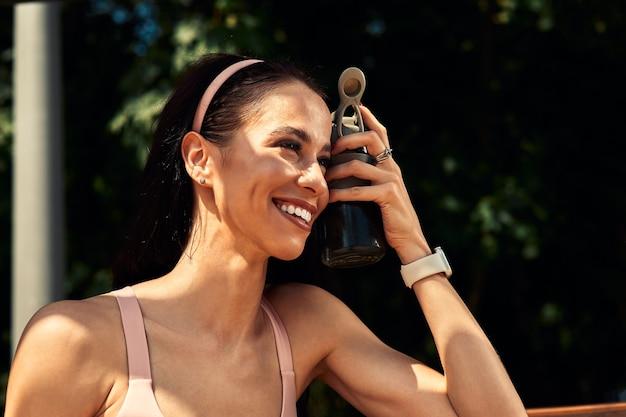 Selbstbewusste, schöne frau, die sich nach dem training im freien ausruht und wasser aus einer flasche trinkt, führt einen gesunden lebensstil.