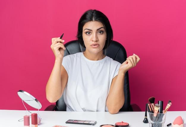 Selbstbewusste schöne frau sitzt am tisch mit make-up-tools, die eyeliner halten