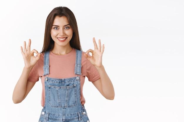 Selbstbewusste, selbstbewusste, gut aussehende frau in denim-overalls, t-shirt, die ein okay-zustimmungszeichen mit einem lächeln zeigt, zustimmen oder eine gute idee akzeptieren, stehend weißer hintergrund erfreut, zufrieden