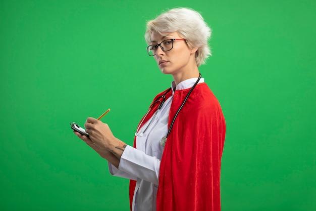 Selbstbewusste slawische superheldenfrau in der arztuniform mit rotem umhang und stethoskop in optischen gläsern steht seitlich und hält klemmbrett und bleistift, die auf grüne wand schauen