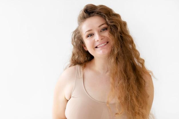 Selbstbewusste smiley-frau, die aufwirft, während sie einen körperformer trägt