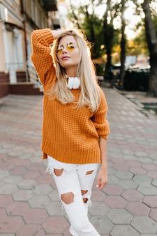Selbstbewusste süße dame in zerrissenen weißen hosen, die mit vergnügen posiert, bevor sie im park spazieren geht