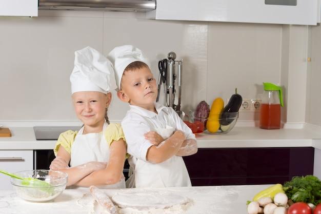 Selbstbewusste süße kinderköche, die essen in der küche zubereiten.