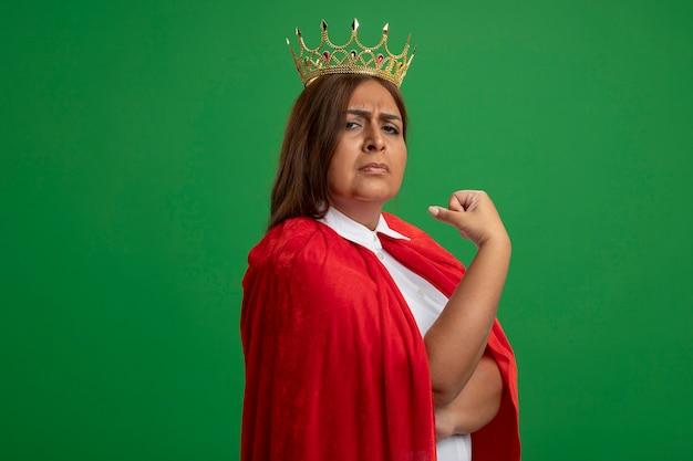 Selbstbewusste superheldenfrau mittleren alters, die kronenpunkte auf sich selbst trägt, isoliert auf grün