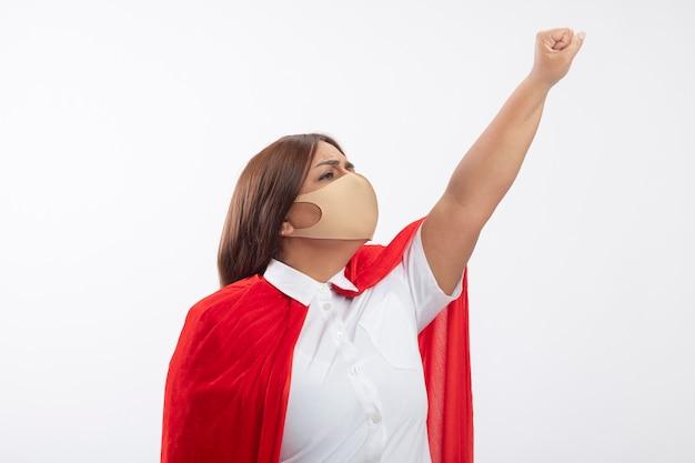 Selbstbewusste superheldenfrau mittleren alters, die medizinische maske trägt, die seite betrachtet, die faust auf weiß isoliert