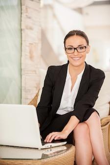 Selbstbewusste und erfolgreiche geschäftsfrau. selbstbewusste junge frau in formeller kleidung, die am laptop arbeitet und lächelt, während sie auf dem bequemen stuhl sitzt