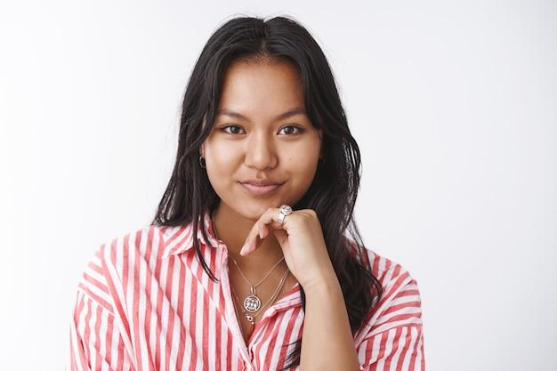Selbstbewusste und mutige, gut aussehende, freche asiatische frau in gestreifter bluse, die das kinn berührt und entschlossen in die kamera schaut und viele interessante und produktive gedanken hat, wie man ein geschäft gründet