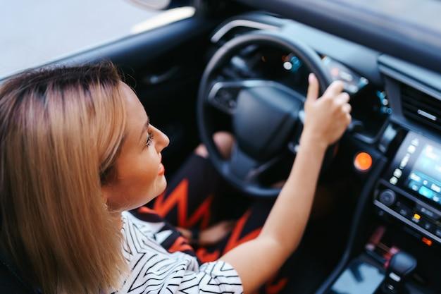 Selbstbewusste und schöne frau mit sonnenbrille. rückansicht der attraktiven jungen frau in der freizeitkleidung, die ein auto fährt