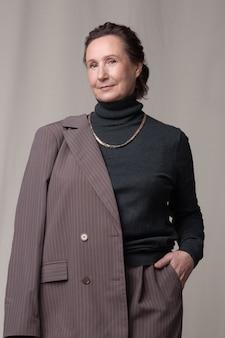 Selbstbewusste und schöne kaukasische frau des höheren alters, die in einem stilvollen anzug im fotostudio aufwirft.