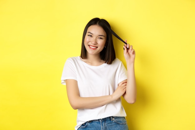 Selbstbewusste und stilvolle asiatische frau kreuzt die arme auf der brust und lächelt, steht auf gelbem hintergrund