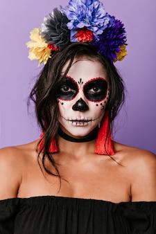 Selbstbewusste zauberin gegen lila wand. mexikanische frau mit körperkunst, die aufwirft.