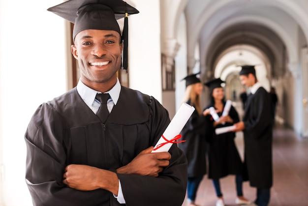 Selbstbewusster absolvent. glücklicher afrikanischer mann in abschlusskleidern, der diplom hält und lächelt, während seine freunde im hintergrund stehen