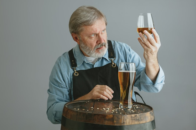 Selbstbewusster älterer mannbrauer mit selbst hergestelltem bier im glas auf holzfass auf grau