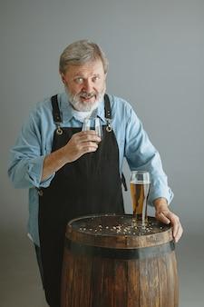 Selbstbewusster älterer mannbrauer mit selbst hergestelltem bier im glas auf holzfass auf grauer wand