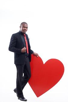 Selbstbewusster afrikanischer mann, der elegante suite und rote krawatte trägt, die von hand auf großes rotes herz lehnt