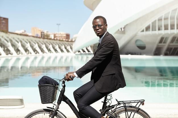 Selbstbewusster afroamerikanischer geschäftsmann in formeller kleidung, der zur arbeit am schwarzen fahrrad pendelt. firmenangestellter eilt mit dem fahrrad ins büro. umweltfreundliches transport- und gesundes konzept für einen aktiven lebensstil