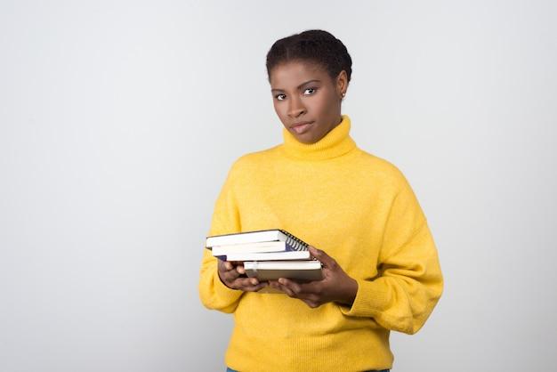 Selbstbewusster afroamerikanischer student, der bücher hält