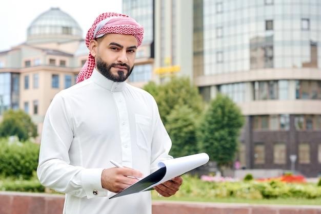 Selbstbewusster arabischer geschäftsmann, der eine zwischenablage mit dokumenten hält