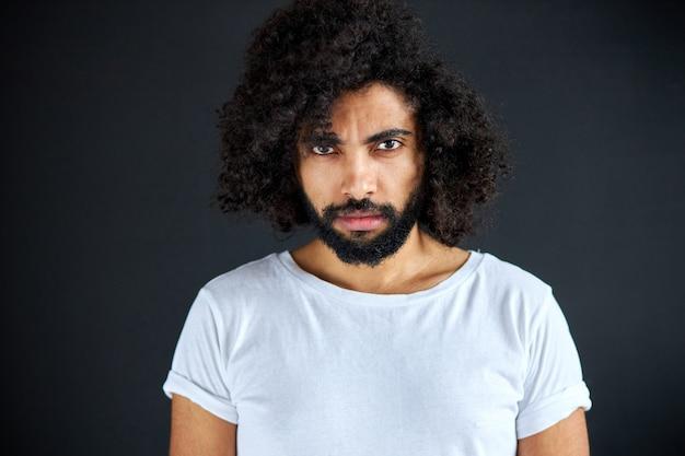 Selbstbewusster arabischer mann im weißen t-shirt mit tiefem blick, blick auf kamera, lockiger kerl ist ernst