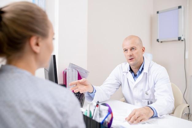 Selbstbewusster arzt im weißen kittel, der am arbeitsplatz sitzt, während er junge patientin konsultiert, die vor ihm sitzt