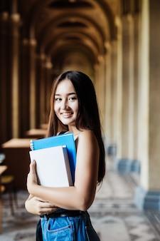 Selbstbewusster asiatischer student, der bücher hält und an kamera-, bildungs-, campus-, freundschafts- und personenkonzept lächelt