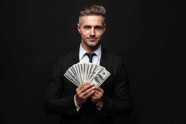 Selbstbewusster attraktiver geschäftsmann im anzug, der isoliert über schwarzer wand steht und geldbanknoten zeigt