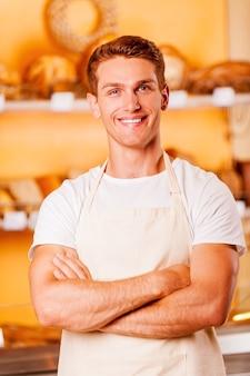 Selbstbewusster bäcker. schöner junger mann in schürze, der die arme verschränkt hält und lächelt, während er in der bäckerei steht?