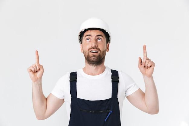 Selbstbewusster bärtiger baumeister mit overall und schutzhelm, der isoliert über weißer wand steht und mit dem finger auf den kopierraum zeigt