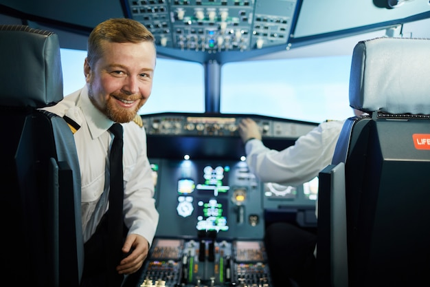 Selbstbewusster bärtiger pilot im cockpit