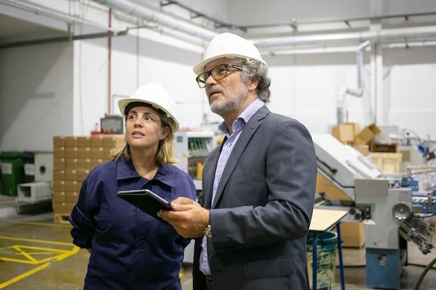 Selbstbewusster bärtiger vorgesetzter, der mit weiblicher fabrikarbeiterin spricht und tablette hält