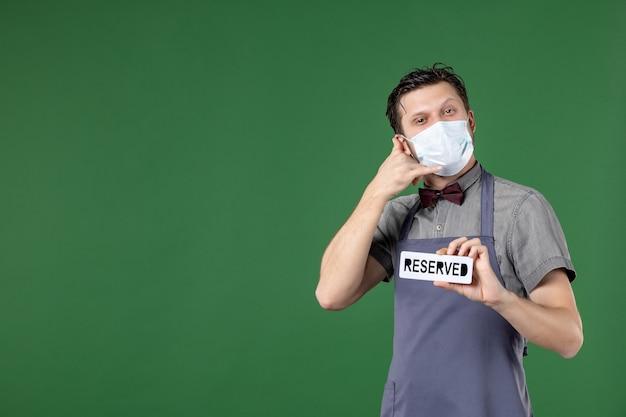 Selbstbewusster bankettserver in uniform mit medizinischer maske und reserviertem symbol, das mich auf grünem hintergrund anruft